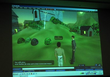 Ekran przedstawiający aplikacje Second Life, na niej rozmawiające postaci na tle wzgórza i budynków